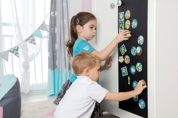 2 Kinder spielen mit Magneten am Wochenplaner von WolffKids